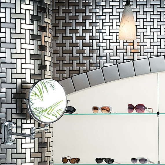 Close up of a wall in an sunglasses shop with stainless-steel metallic-look tile mosaic in a basketweave pattern on the wall with shelves of designer sunglasses displayed.