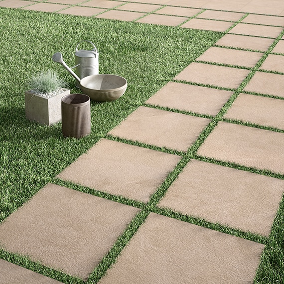 Outdoor walkway made of 2 cm porcelain gray stone look pavers laid on thick green grass.