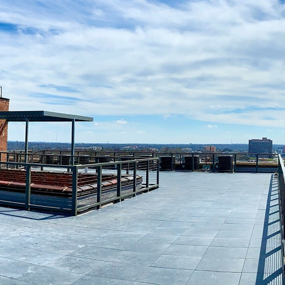 Rooftop with 2CM, gray stone look pavers, metal rails, air conditioner units, and a blue sky background with white fluffy clouds.