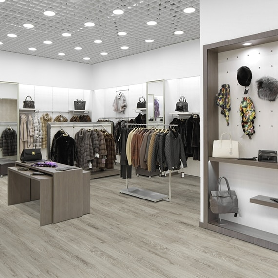 Retail clothing store with luxury vinyl flooring that looks like light gray wood floor, racks with clothing, and hats hanging from a peg board.