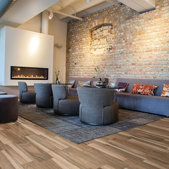 Lobby with wood look tile floor, blue area rug, chairs, and sofas, wall mounted electric fireplace, and brick wall.