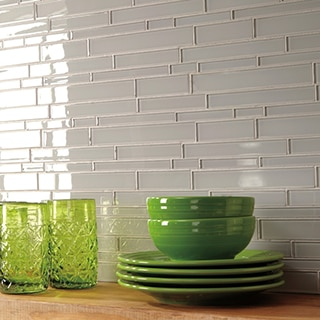 Closeup of gray glass mosaic tile backsplash with floating wood-grain shelf holding bright green plates, bowls, and drinking glasses.