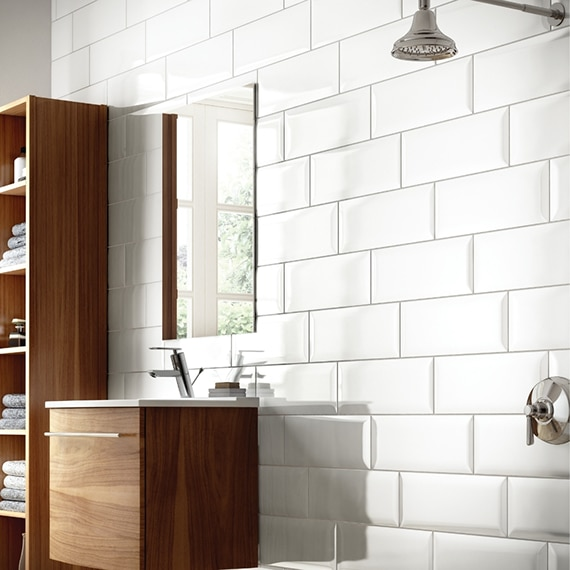 Bright bathroom with white beveled subway tile backsplash, polished silver faucets, and wood-grain shelf and floating vanity.