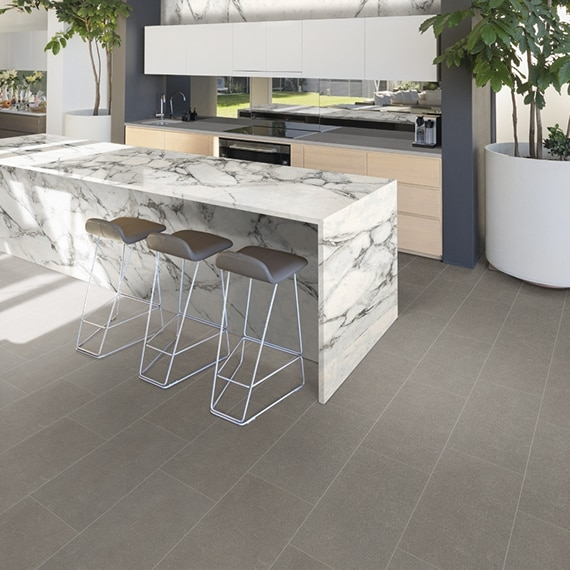 Minimalistic wet bar with gray, 12x24 concrete look floor tile is dressed up with marble look porcelain slab on the waterfall island countertop.