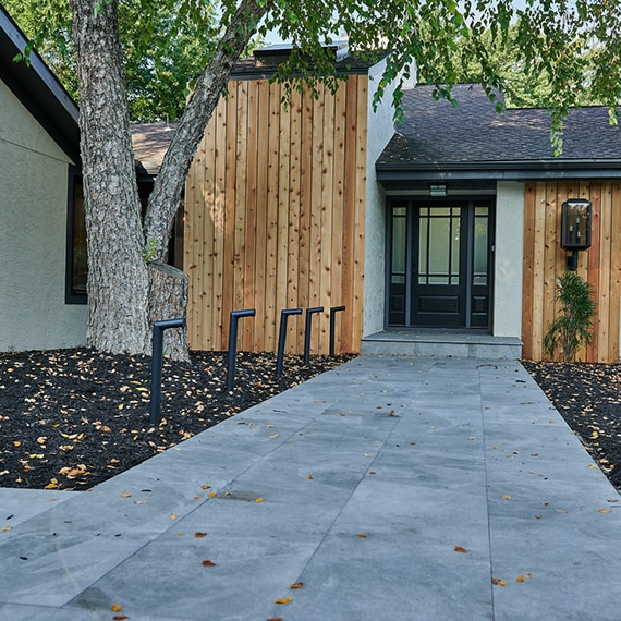 Home entrance with black & glass door, white stucco, wood panel accents, walkway with light gray 2CM porcelain pavers, and large tree.