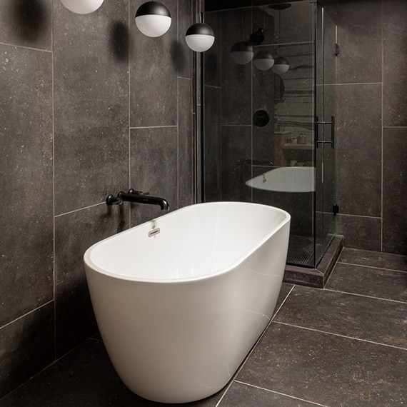 Freestanding bathtub and separate walk-in shower with dark gray, large format, stone look floor tile and wall tile, and round pendant lighting.