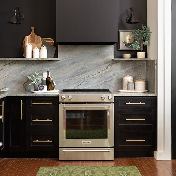 Kitchen with gray natural quartzite backsplash, floating shelves, and countertop, stainless steel stove, black hood vent.
