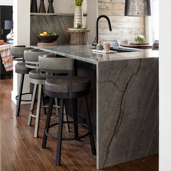 Kitchen with gray natural quartzite island with sink and waterfall countertop, gray leather and metal bar stools, pendant lighting.