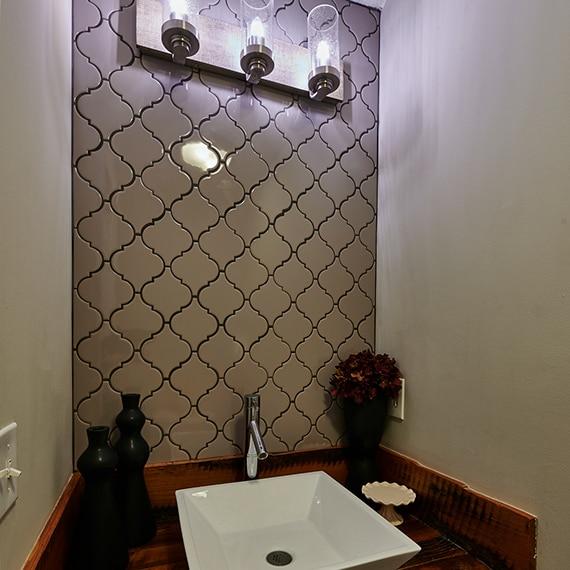 Bathroom vanity with gray arabesque backsplash, wood & metal lighting, wood countertop, desk mounted sink, polished silver faucet.