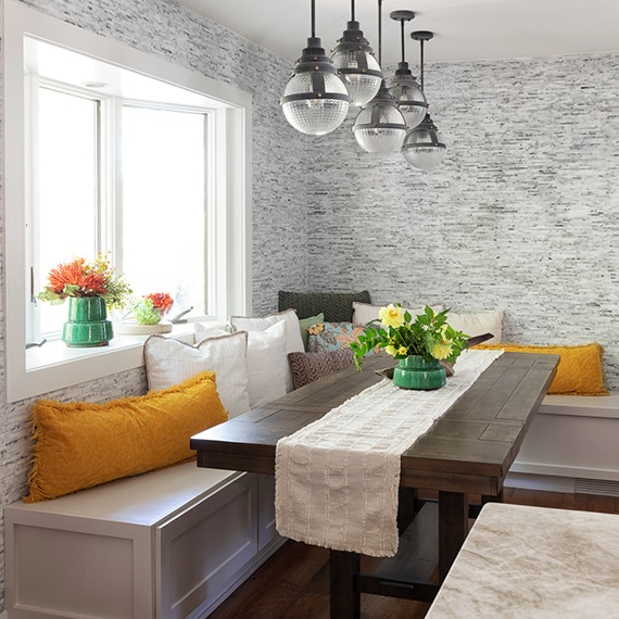 Banquette covered with throw pillows, wood table, pendant lighting and linear marble mosaic wall tile, bay window with flower pots.