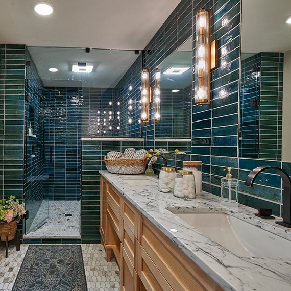 Bathroom with teal glazed porcelain wall tile, marble countertop, natural wood cabinets, elongated hex mosaic marble floor tile.