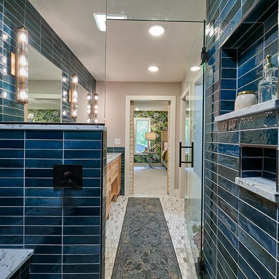 Shower with blue glazed porcelain wall tile, marble shelves & bench, brass & glass sconces, elongated hex mosaic marble floor tile.