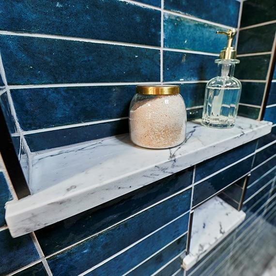 Closeup of shower niches with blue glazed porcelain wall tile, marble shelf holding bath salt & glass liquid soap dispenser.