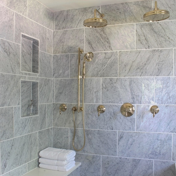 Elegant shower with large format gray marble with white marble bench, two shower niches, brass showerheads and brass fixtures.