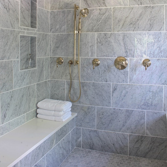Renovated bathroom with wet room of gray marble wall tile, marble mosaic floor tile, and polished brass fixtures.