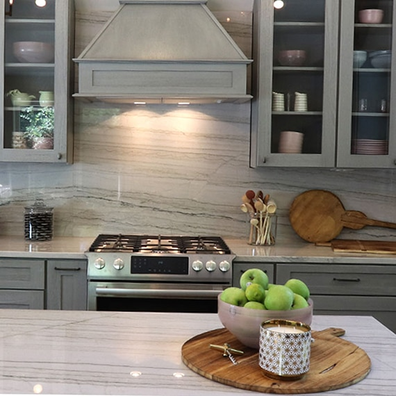 Renovated kitchen with heavily veined gray quartzite backsplash, island, and countertop, gray cabinets, and stainless steel gas stove.