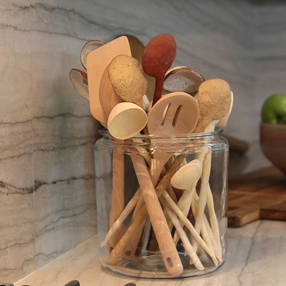 Closeup of glass jar with wooden spoons on a taupe natural quartzite countertop.