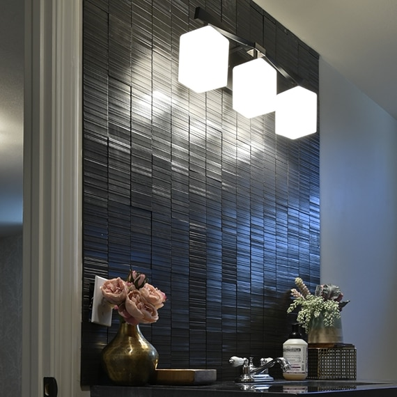 Textured black metal tile backsplash with three hanging lights, black quartzite countertop sink with small bouquet of pink roses.