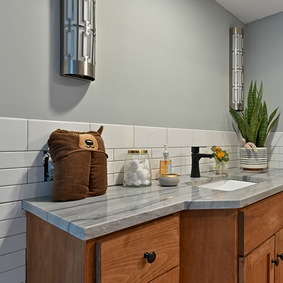 Children's bathroom with gray quartzite countertop with heavy striations on a vanity of natural wood cabinets, and white ceramic tile backsplash/wainscot.