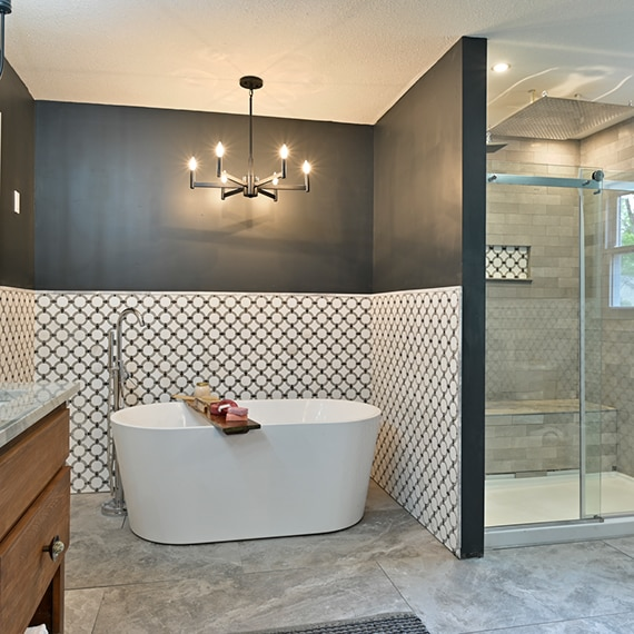 Bathroom with free standing bathtub in front of wainscoting of white marble tile with gray rings and shower with gray tile and niche with matching marble tile with rings.