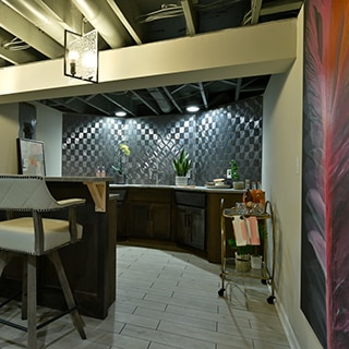 Basement bar with silver textured geometric wall tile that looks like metal tile, floor tile that looks like wood flooring, and beige leather bar stools.