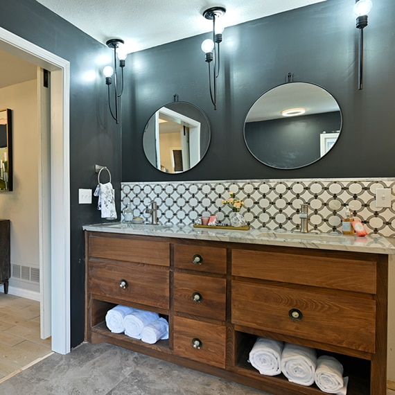 Bathroom with gray marble look floor tile, black walls, wainscoting of white marble tile with gray rings, and wood vanity with quartzite countertop.