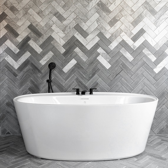 Freestanding soaking bathtub in front of chevron backsplash of white & gray marble tile blended with gray limestone tile.