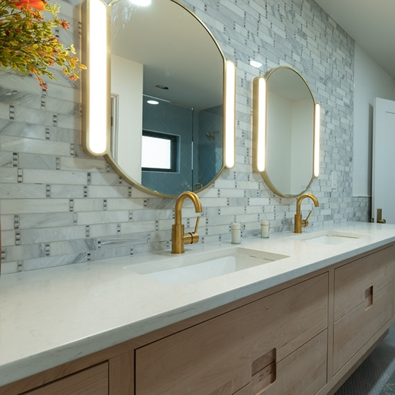 Bathroom quartz countertop with double sinks, brushed brass faucets, marble mosaic backsplash, and lighted vanity mirrors.