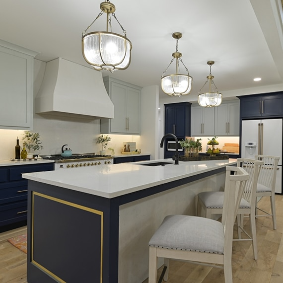 Kitchen with white upper cabinets, navy lower cabinets, white quartz countertops, island with sink, glass & brushed brass pendant lights.