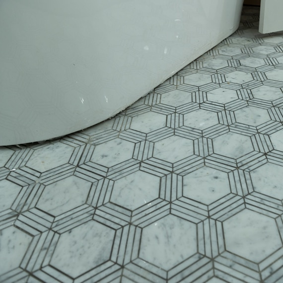 Closeup of white with gray veining marble hexagon mosaic tile and gray grout, next to freestanding bathtub.
