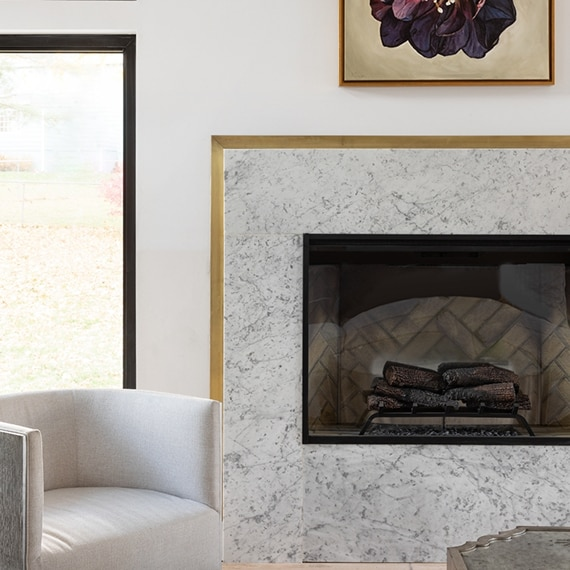 Fireplace with gray & white marble surround and brushed brass trim.