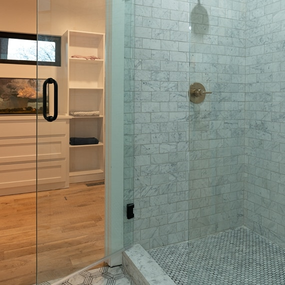 Shower with white with gray veining marble 3x6 tile, marble oval mosaic shower floor tile, brushed brass fixtures, and glass door.