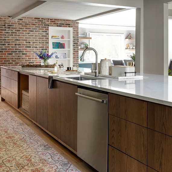 Kitchen island with under mount sink, nickel faucet, white quartz countertop, natural wood base, with built-in dishwasher.