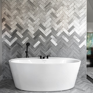 Freestanding soaking tub in front of chevron backsplash of white & gray marble tile blended with gray limestone tile, and matte black faucet.