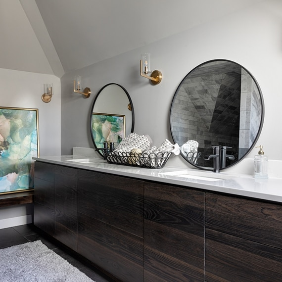 Bathroom double vanity with round mirrors, brass wall sconces, wire basket with rolled towels, white quartz countertop over dark wood cabinets.