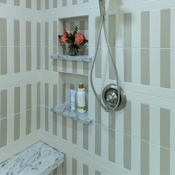 Shower with cream & tan striped wall tile, white & gray marble shower niche shelves, brushed nickel fixtures and white & gray marble bench.