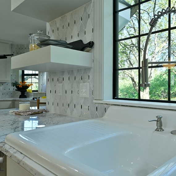 Farmhouse kitchen sink on white marble countertop, antique mirror & marble mosaic backsplash, white floating shelves and picture window.
