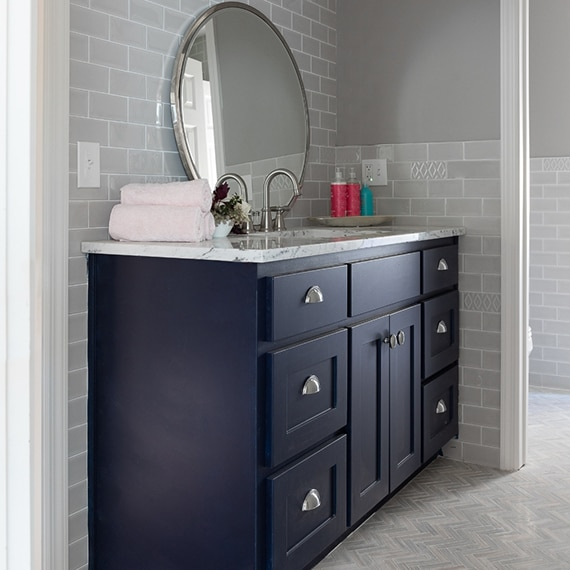 Bathroom vanity with gray subway tile backsplash & wainscoting, round mirror, nickel faucet, rolled towels on navy cabinets.