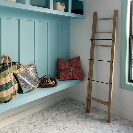 Mudroom with wood ladder, gray & white marble hex mosaic floor tile, light blue bench and shelves, holding beach bags and blankets.