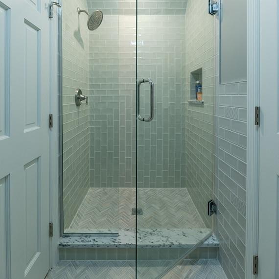 Shower with light green tile, nickel fixtures, marble niche & threshold, herringbone mosaic gray/tan marble shower floor tile.