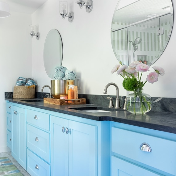 Double bathroom vanity with 2 round mirrors, black soapstone countertop with 2 sinks over light blue cabinets with silver fixtures.