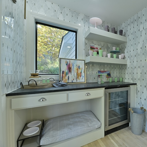 Kitchen coffee nook with antique mirror & marble mosaic wall tile, floating shelves, black soapstone countertop, pet cubby, and under counter wine fridge.