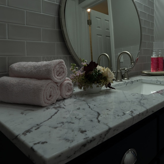 Bathroom vanity with gray subway tile backsplash, white marble with dark gray veining countertop, rolled towels and small flower bouquet.
