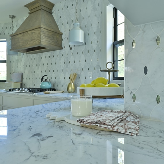 Kitchen with white marble countertops with gray veining, antique mirror & marble mosaic backsplash, wooden hood vent over gas stovetop.