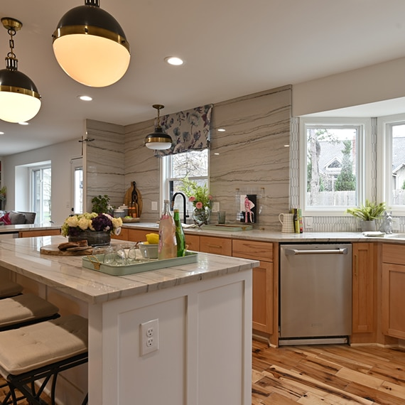 Remodeled kitchen with gray heavily veined quartzite countertop, backsplash, and island, natural wood cabinets, white picket wall tile frames the bay window.