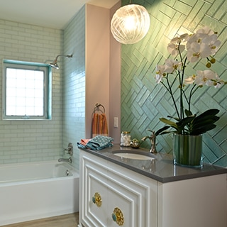 Small bathroom with light green glass tile backsplash, vanity with gray quartz counter and silver faucet, and mint glass subway shower tile.