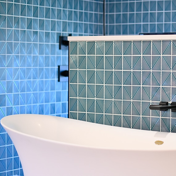 Closeup of blue geometric shower tile and wainscot tile behind a free-standing white bathtub with black faucet.