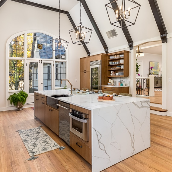 Remodeled kitchen with high vaulted ceiling, large picture windows, white & gray marble look quartz waterfall island and backsplash, wood cabinetry and wood beams..