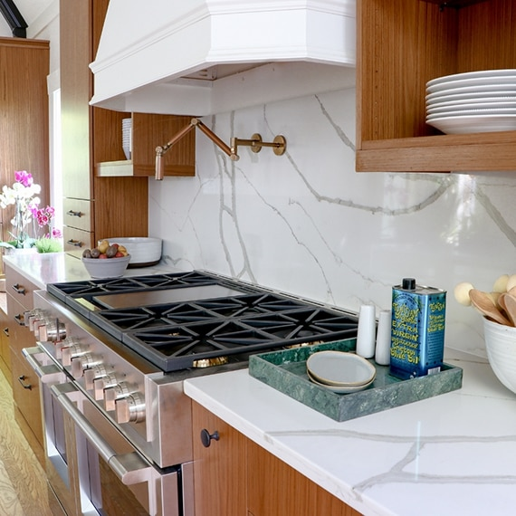 Remodeled kitchen with white & gray marble look quartz countertop & backsplash, stainless steel gas stove, wood cabinetry and floating shelves.
