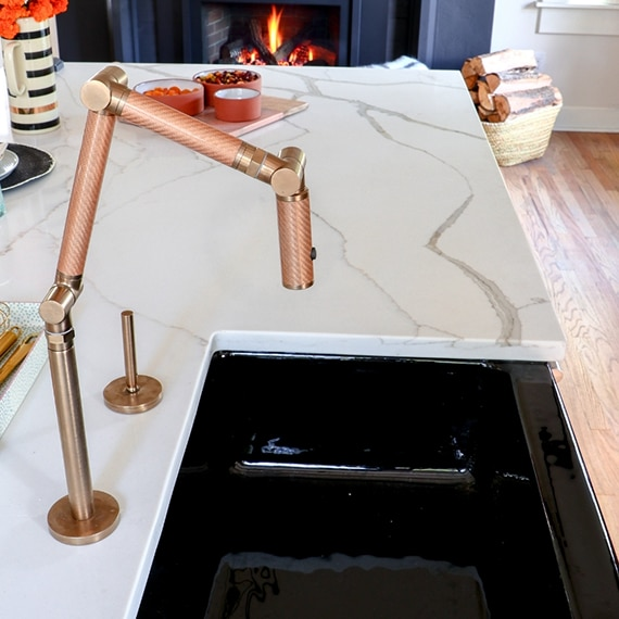 Closeup of white & gray marble look quartz island with black sink, and copper faucet.